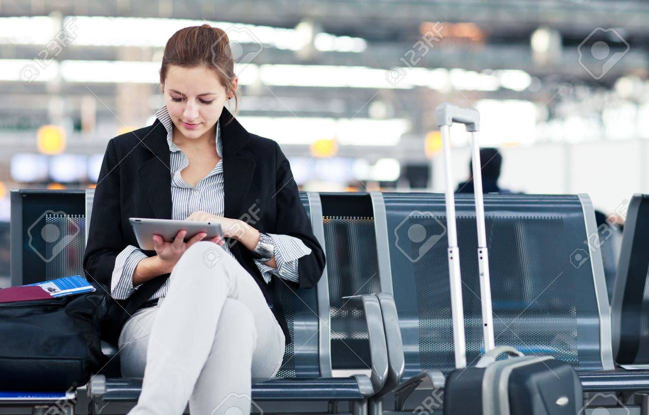 Young female passenger at the airport, using her tablet computer while waiting for her flight (color toned image) Stock Photo - 14108945