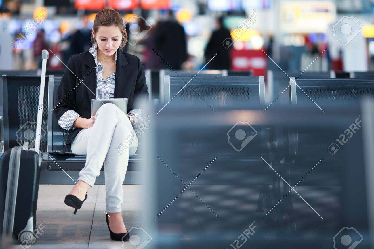 Young female passenger at the airport, using her tablet computer while waiting for her flight (color toned image) Stock Photo - 14108903