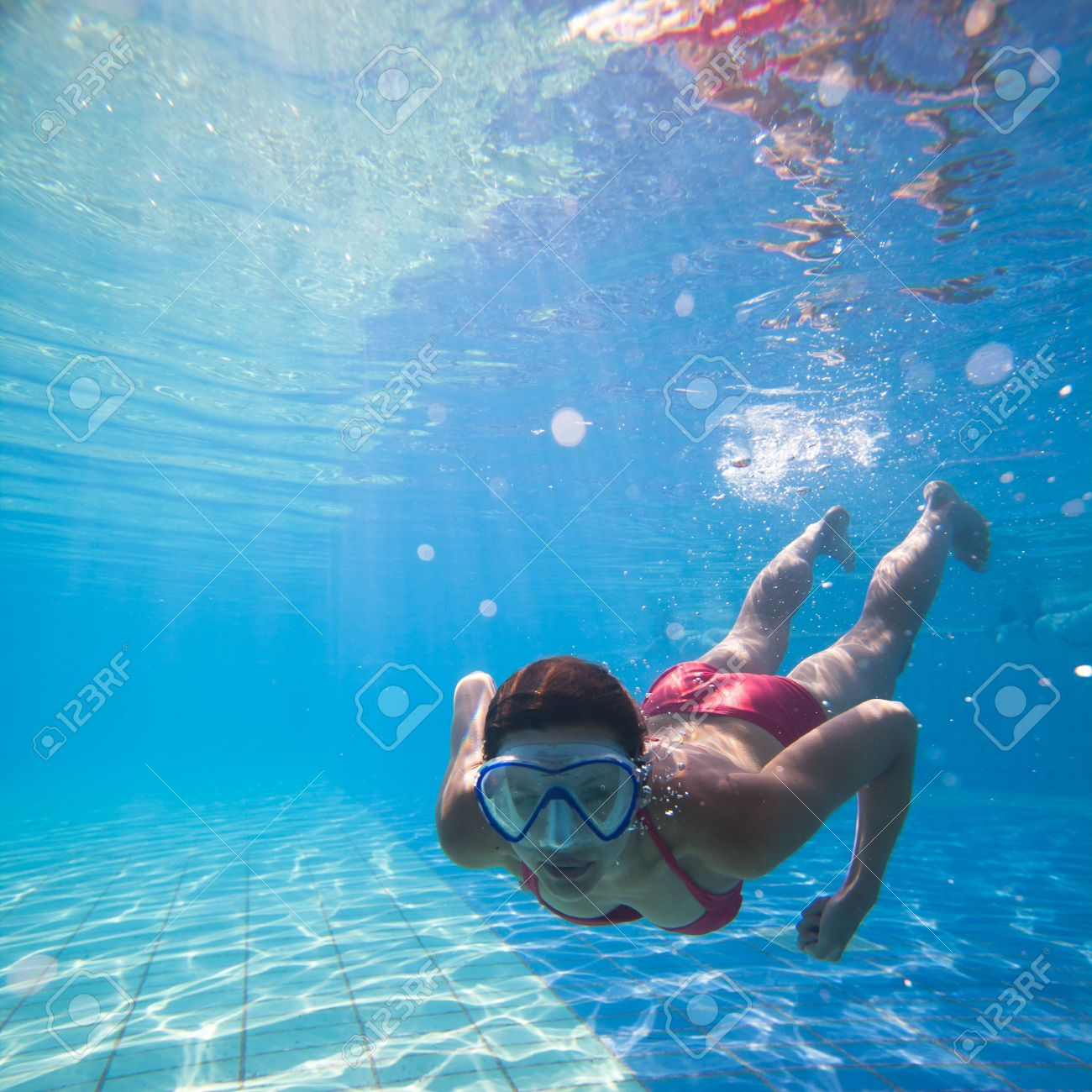 Underwater swimming: young woman swimming underwater in a pool, wearing a diving mask Stock Photo - 14196630