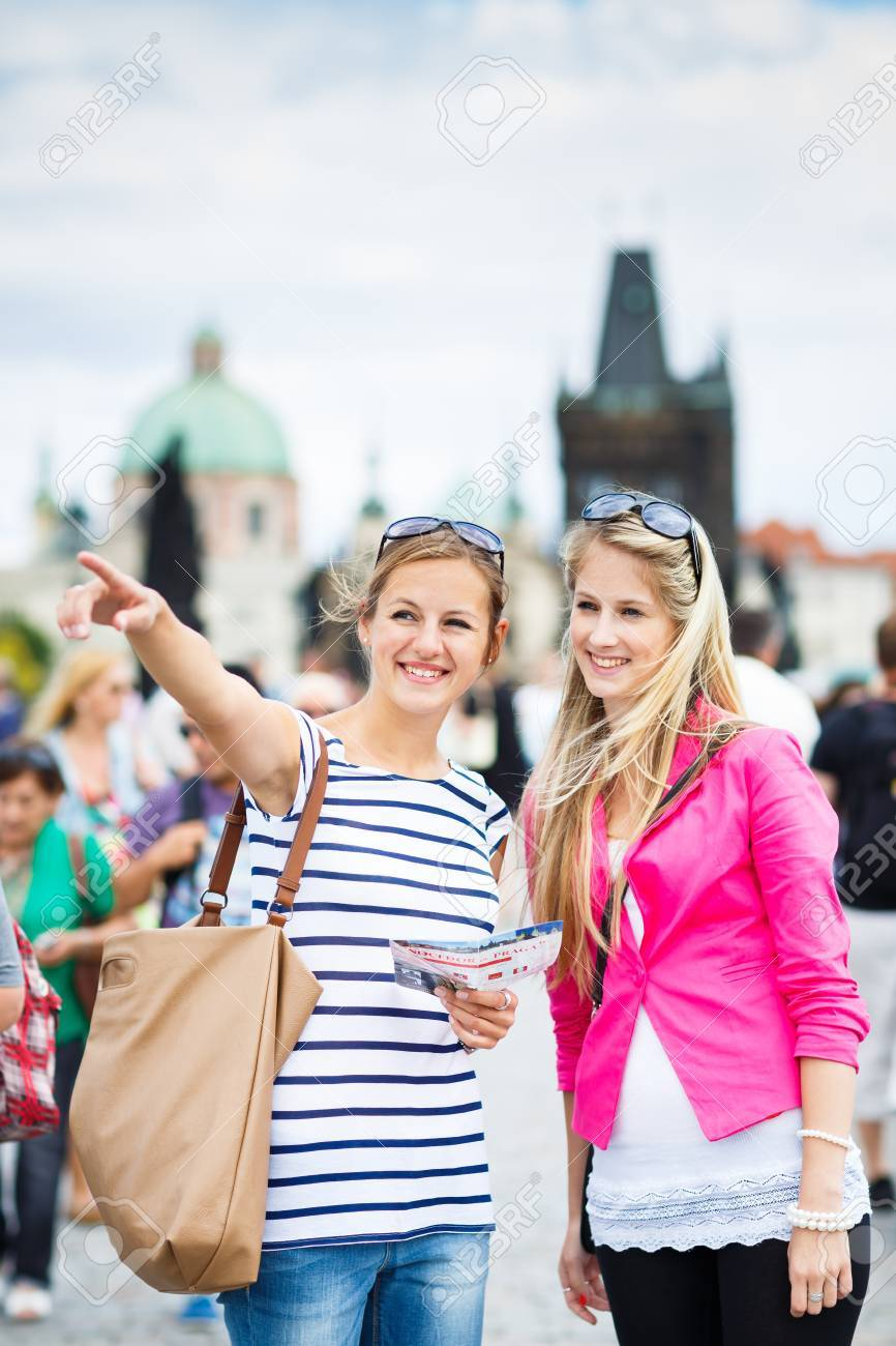 Two female tourists walking along the Charles Bridge while sightseeing in Prague, the historical capital of the Czech Republic Stock Photo - 17133585