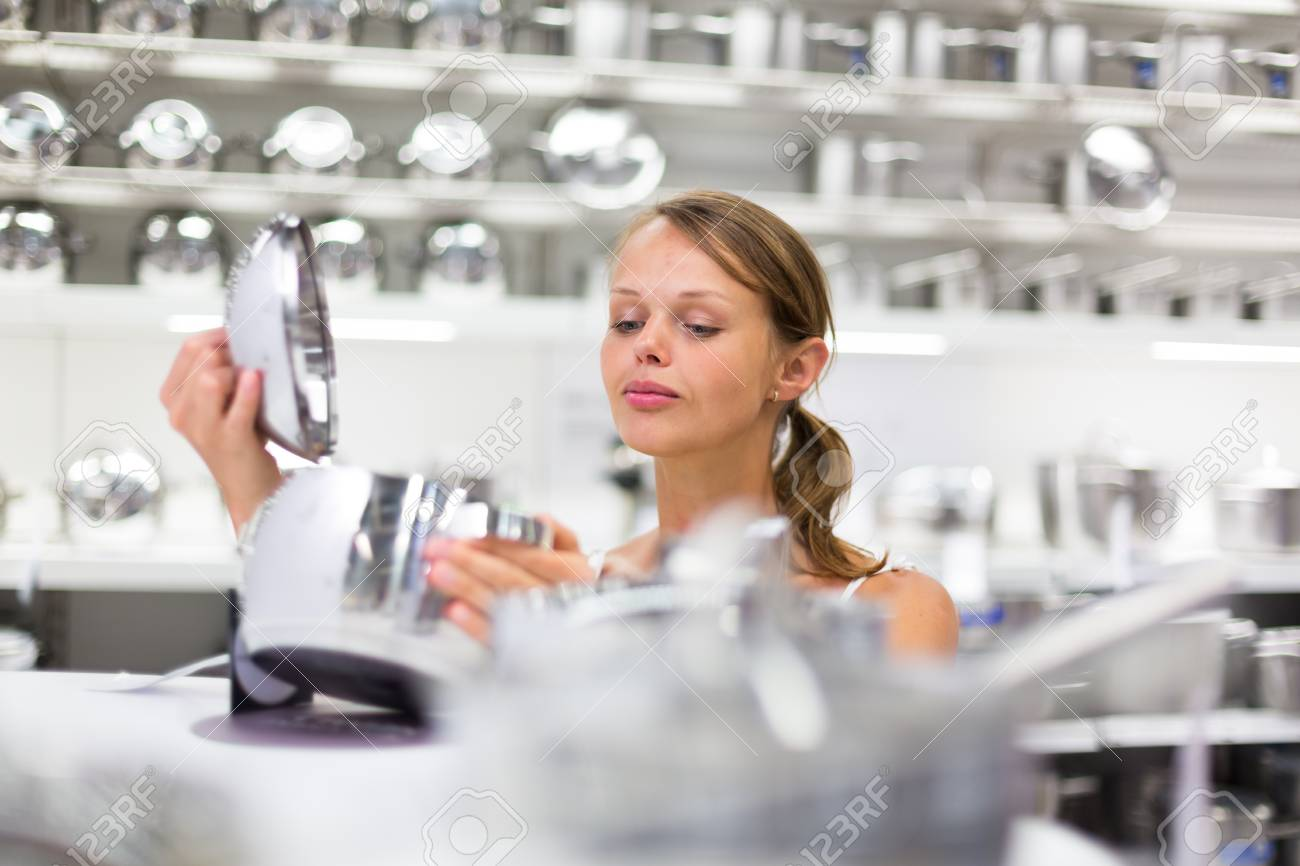 Pretty, young woman choosing a the right pot for her cooking in a modern home furnishings store  color toned image; shallow DOF Stock Photo - 21461935