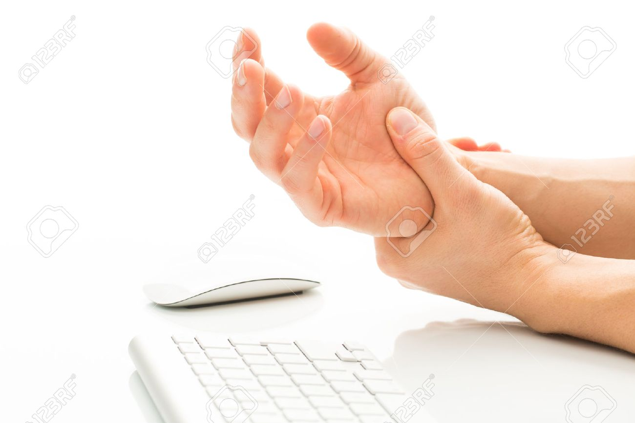 working too much suffering from a carpal tunnel syndrome stock photo working too much suffering from a carpal tunnel syndrome young man holding his wrist in pain due to prolonged use of keyboard and mouse