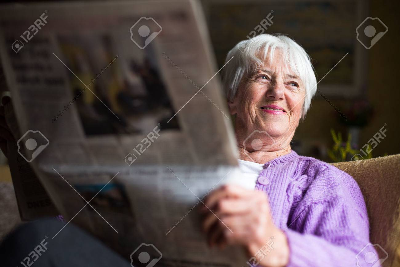 Senior woman reading morning newspaper, sitting in her favorite chair in her living room, looking happy Standard-Bild - 39041595