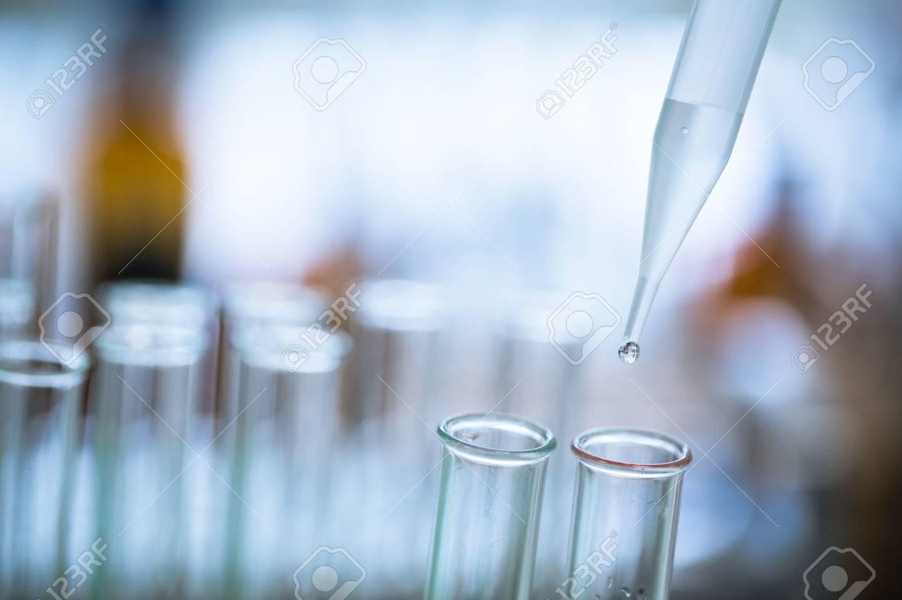 Liquid drop from laboratory glass pipette to test tube Standard-Bild - 38423148