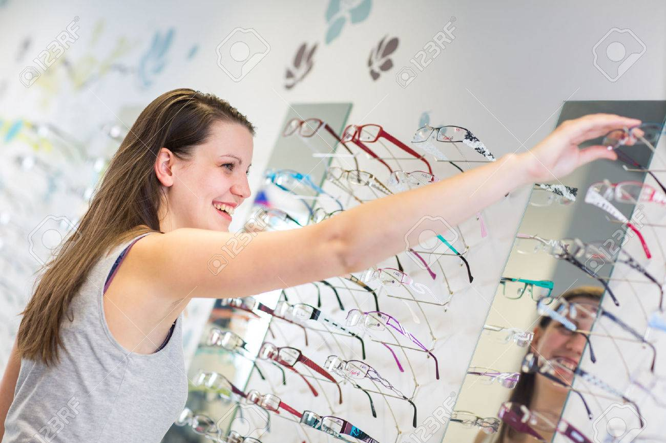 Pretty, young woman choosing new glasses frames in an optician store (color toned image; shallow DOF) Standard-Bild - 45397292
