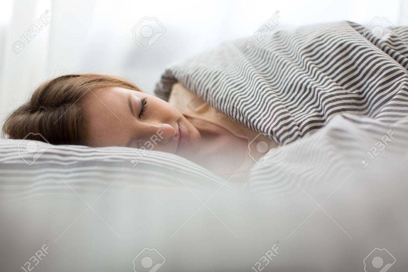 Belle jeune femme dormir dans son lit Banque d'images - 45397382