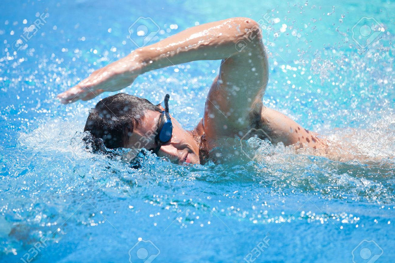 Young man swimming the front crawl in a pool Standard-Bild - 46136102