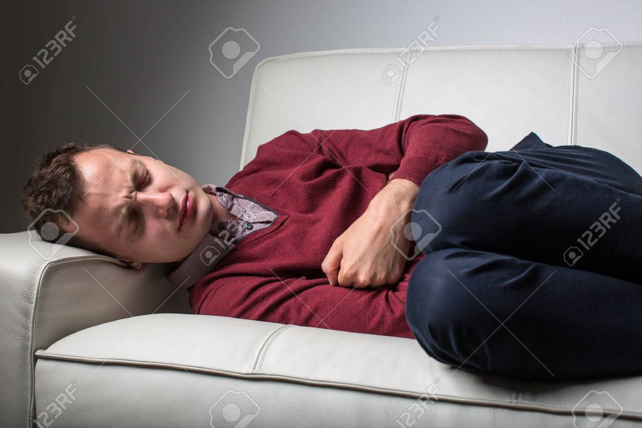 Young man suffering from severe belly pain, being cornered by the debilitating condition of celiac disease/Crohn's disease Standard-Bild - 48151896