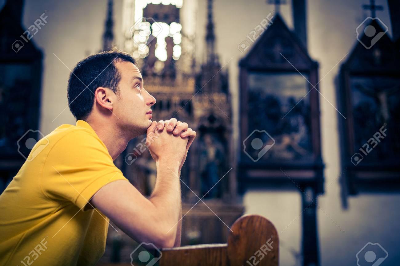 Beau jeune homme en prière dans une église Banque d'images - 50111420