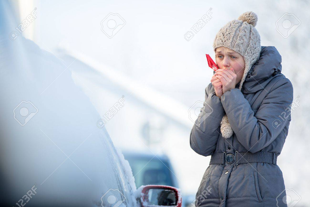 Young woman cleaning her car from snow and frost on a winter morning, she is freezing and needs to get to work - 50640377