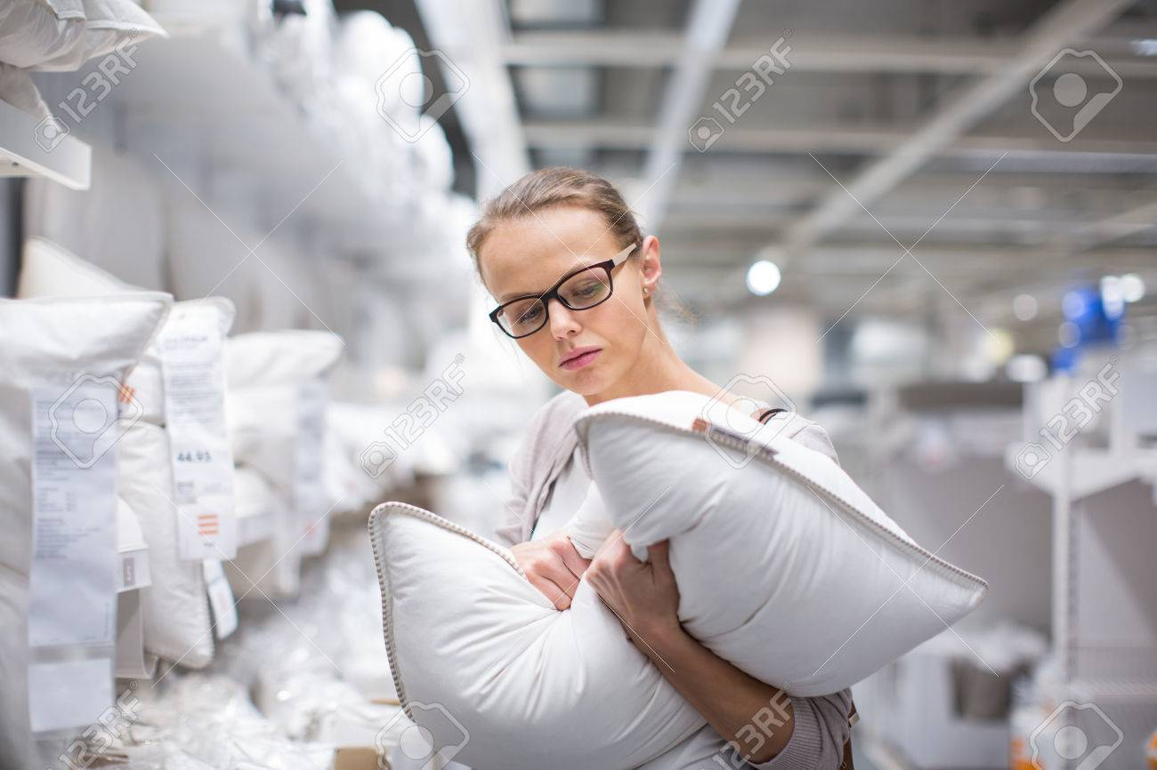 Pretty, young woman choosing the right pillow for her bed in a modern home furnishings store (color toned image; shallow DOF) - 50640652