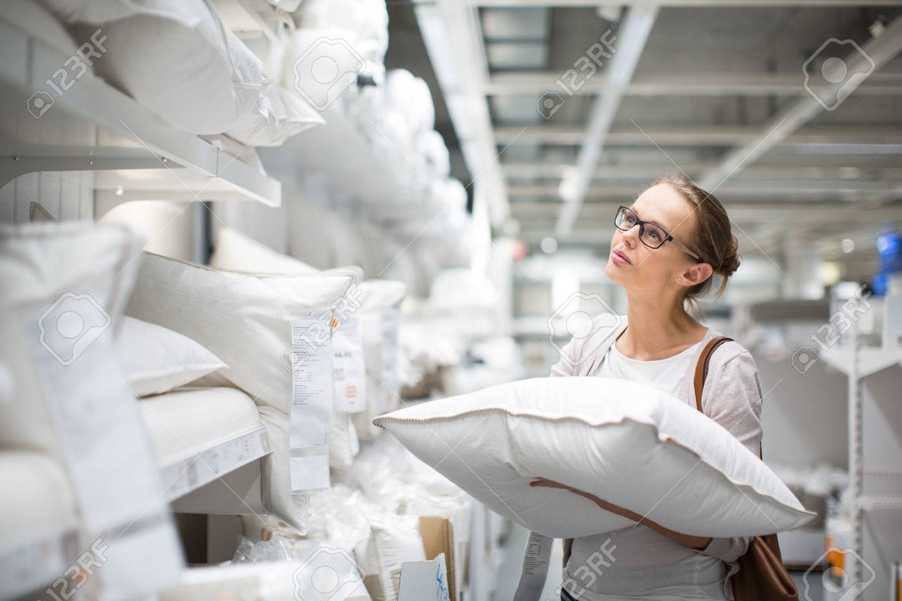 Pretty, young woman choosing the right pillow for her bed in a modern home furnishings store (color toned image; shallow DOF) - 50699189