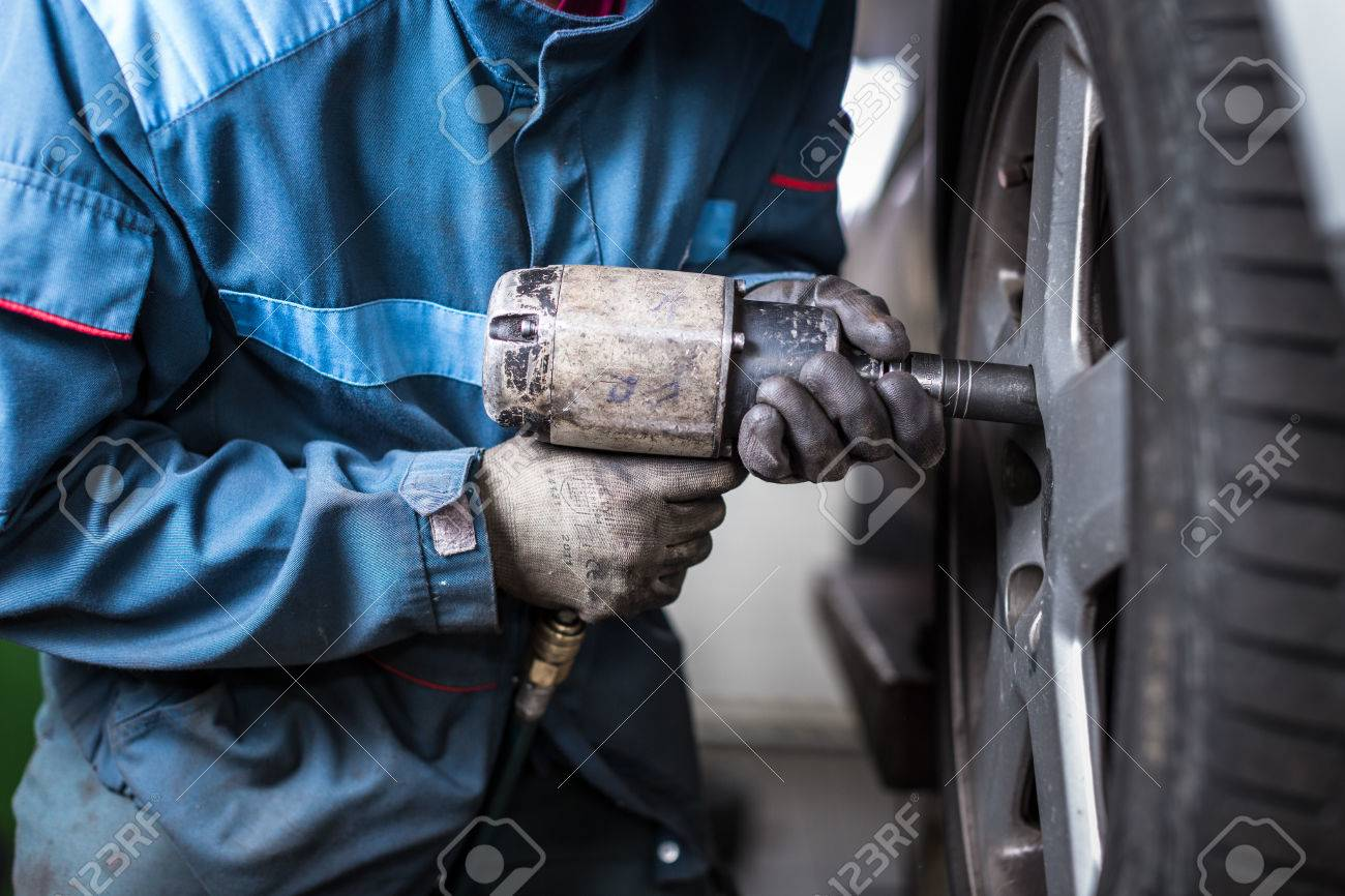 mechanic changing a wheel of a modern car (color toned image) - 51207147