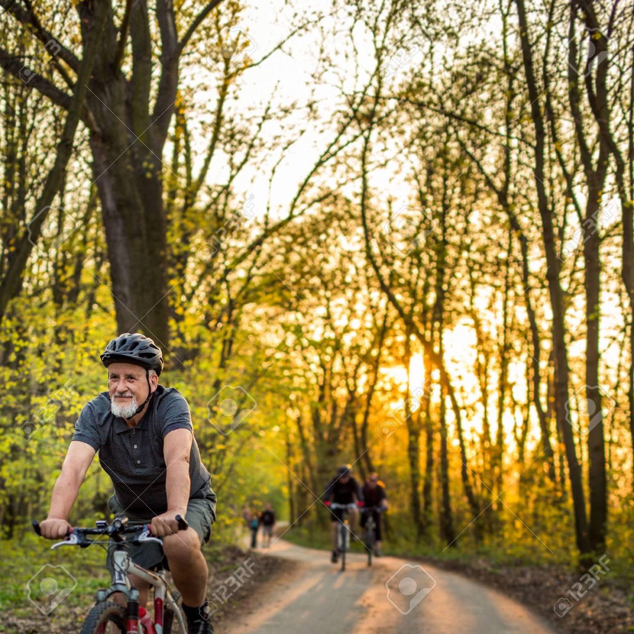Senior man on his mountain bike outdoors (shallow DOF; color toned image) - 54568150