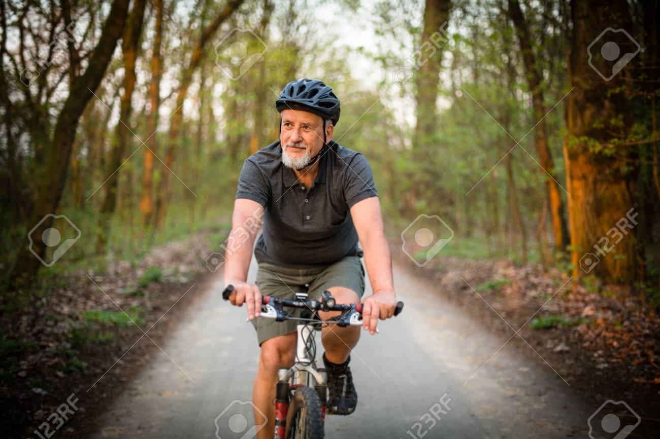 Senior man on his mountain bike outdoors (shallow DOF; color toned image) - 54568373