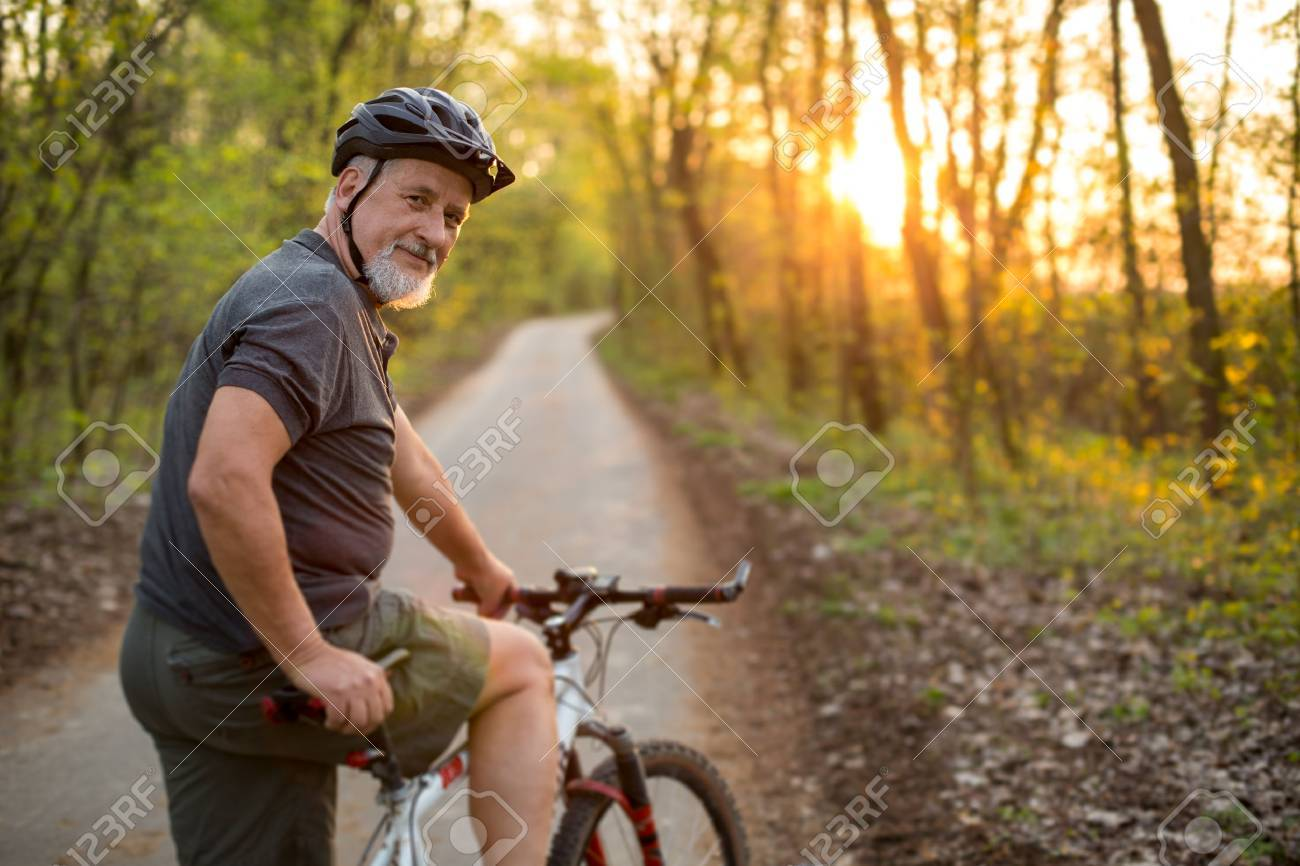 Senior man on his mountain bike outdoors (shallow DOF; color toned image) Standard-Bild - 54568426