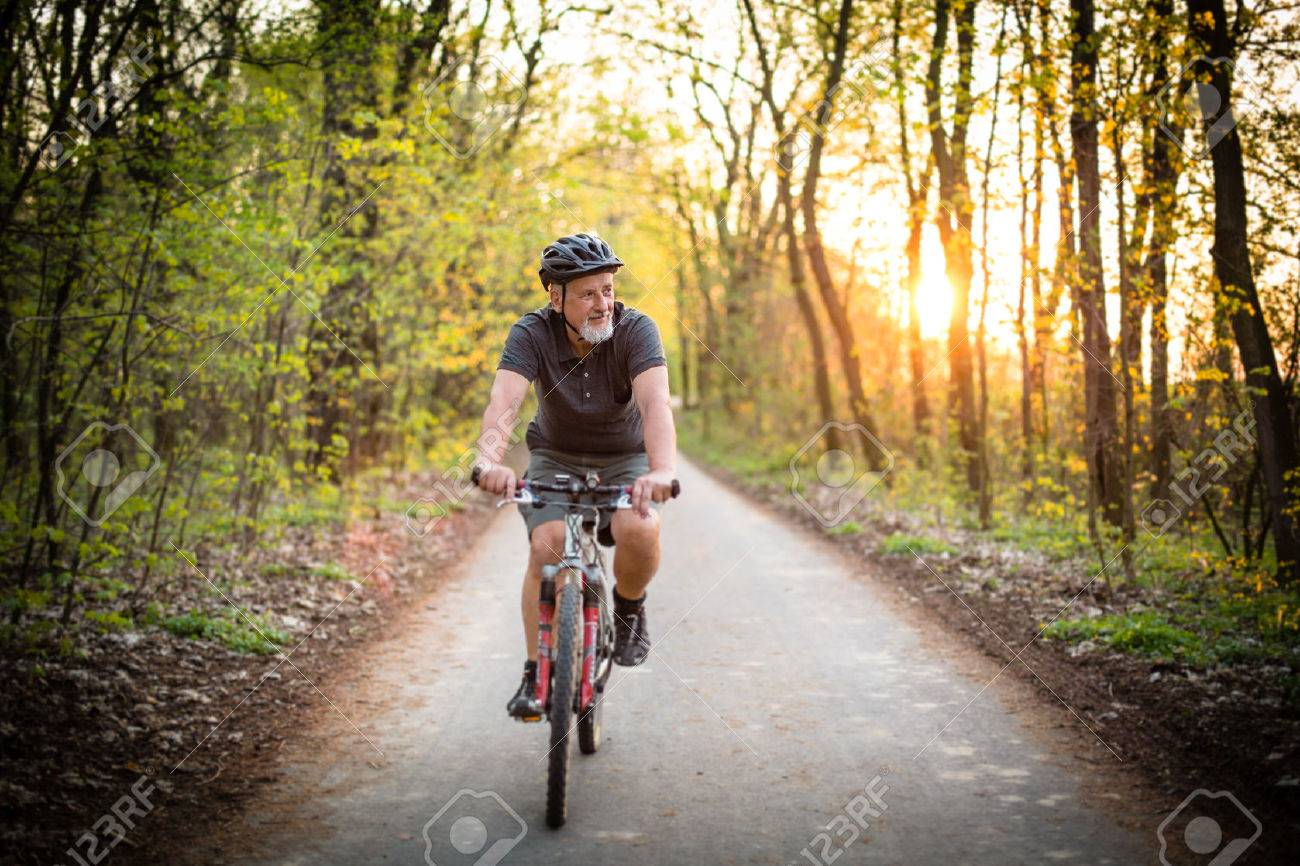 Senior man on his mountain bike outdoors (shallow DOF; color toned image) Standard-Bild - 54568470