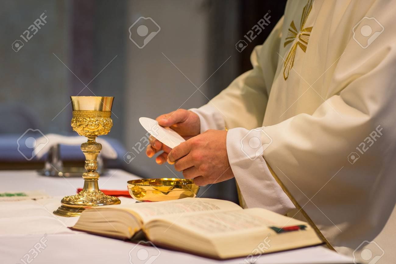 Priest during a wedding ceremony/nuptial mass (shallow DOF; color toned image) Standard-Bild - 64321210