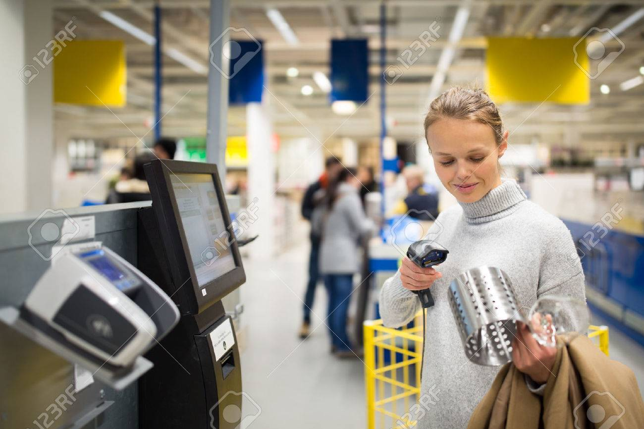 Pretty, young woman using self service checkout in a store (shallow DOF; color toned image) Standard-Bild - 70168728
