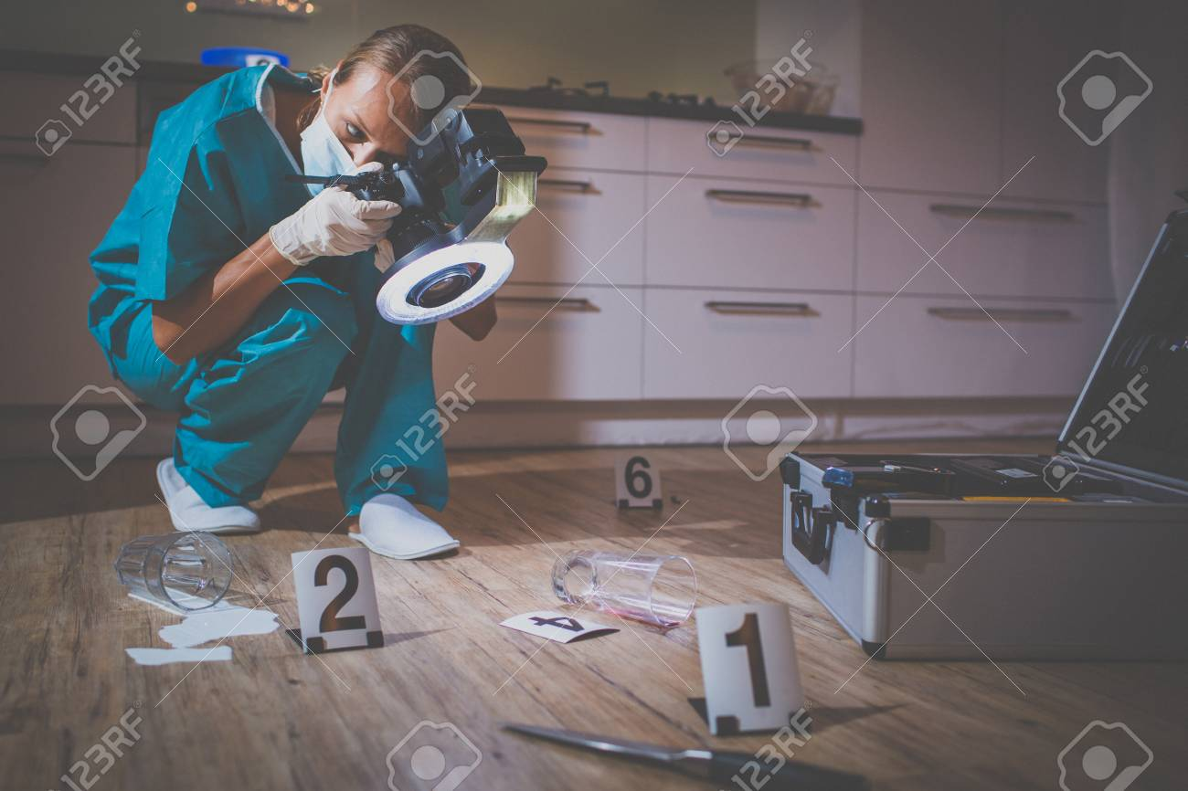 Forensic specialist in protective suit taking photos on a crime scene - 106902016