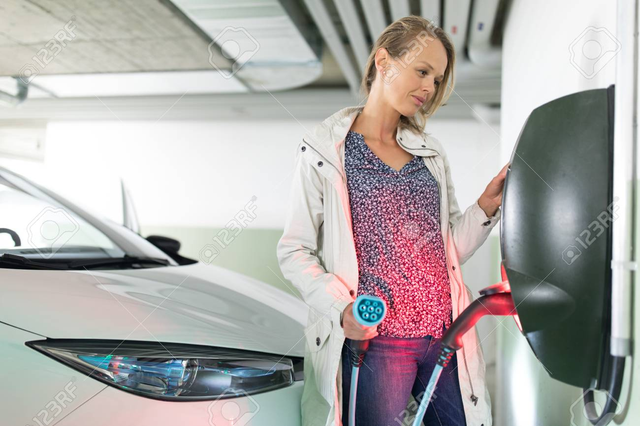 Young woman charging an electric vehicle in an underground garage equiped with e-car charger. Car sharing concept. - 118590883
