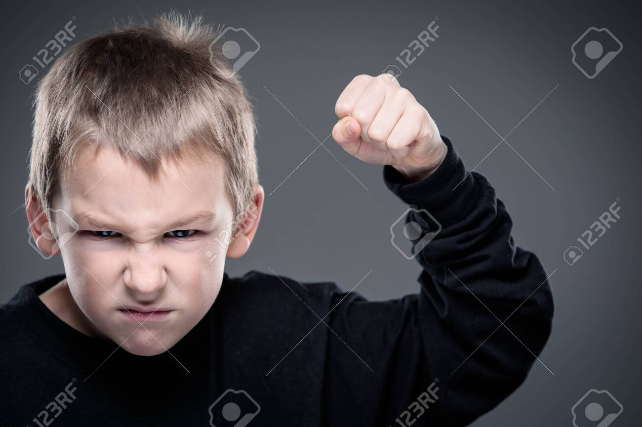 Loads of aggression in a little boy - education concept hinting behavioral problems in young children (shallow DOF) - little boy with hands clenched into fists about to punch someone - 123494473