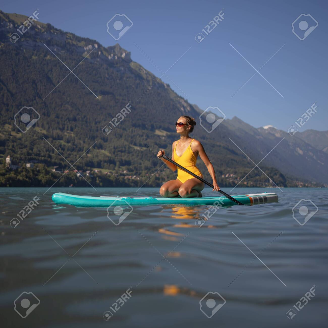 Pretty, young woman paddling on a paddle board on a lake, enjoying a lovely summer day - 141971261