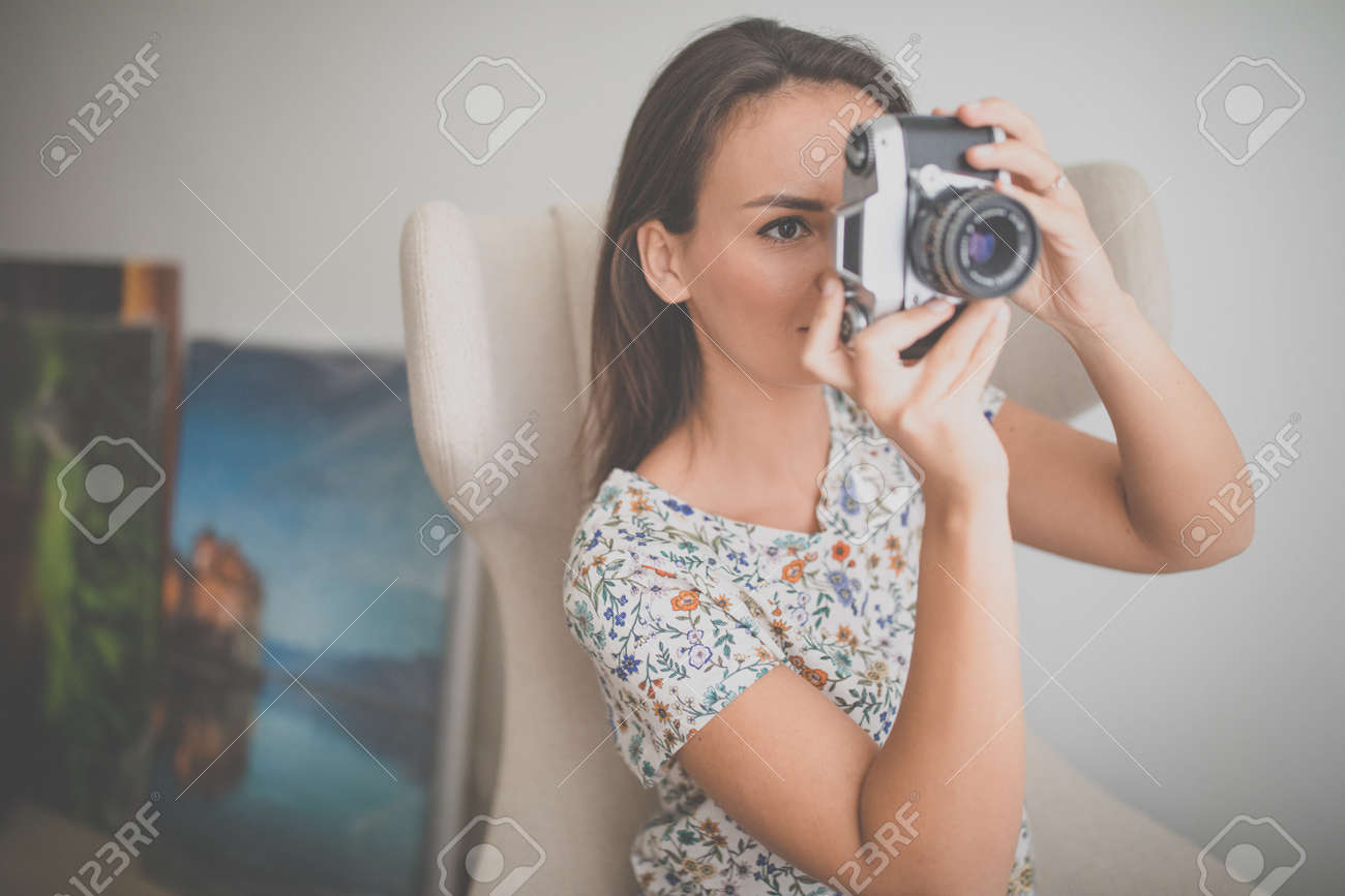 Pretty, young female photographer in her studio taking photos with a vintage film camera (color toned image) - 169294148