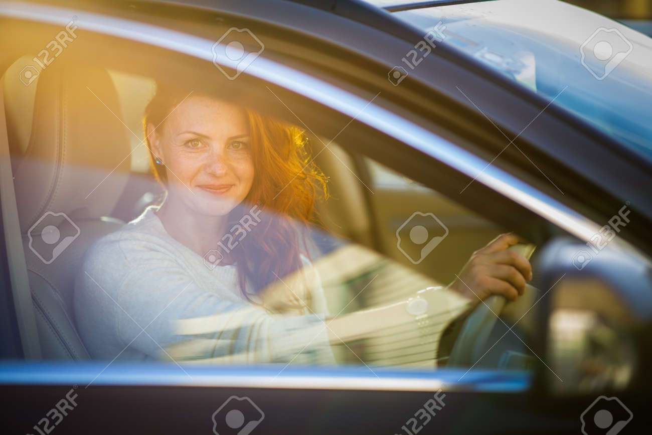 Pretty, young woman driving a car -Invitation to travel. Car rental or vacation. - 171623459