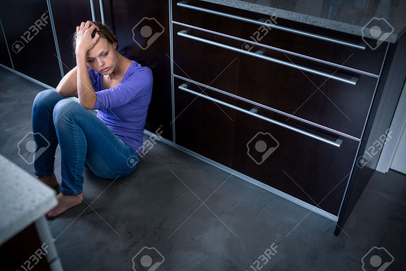 Depressed young woman sitting on the kitchen floor, feeling down - 171623461
