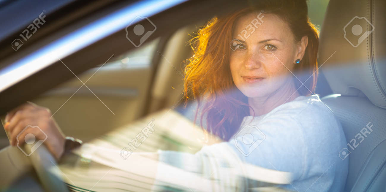 Pretty, young woman driving a car -Invitation to travel. Car rental or vacation. - 171623500