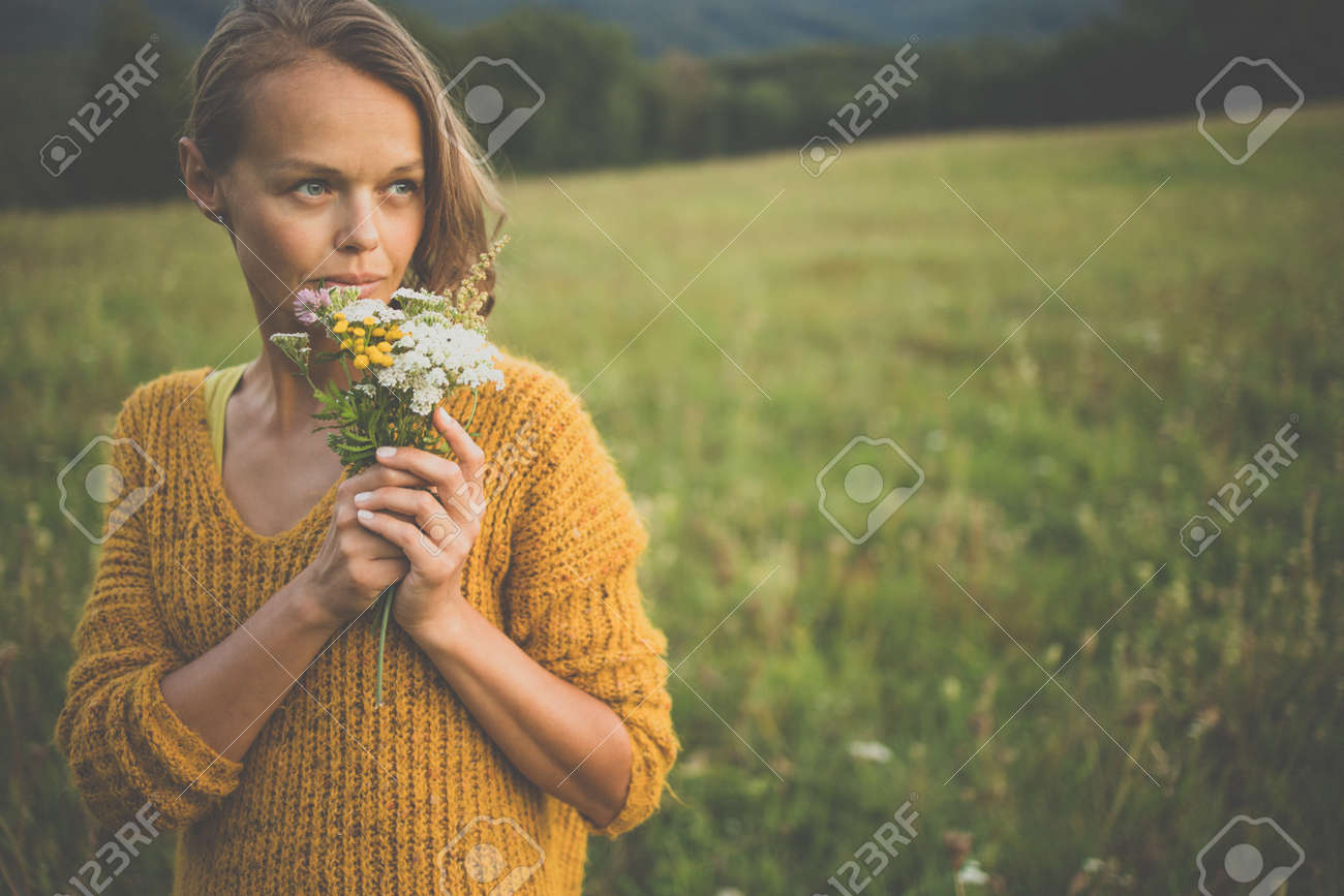 Beautiful young woman outdoors with a bouquet of wild flowers in a field, enjoying nature. Happy Woman on spring meadow - 171623511