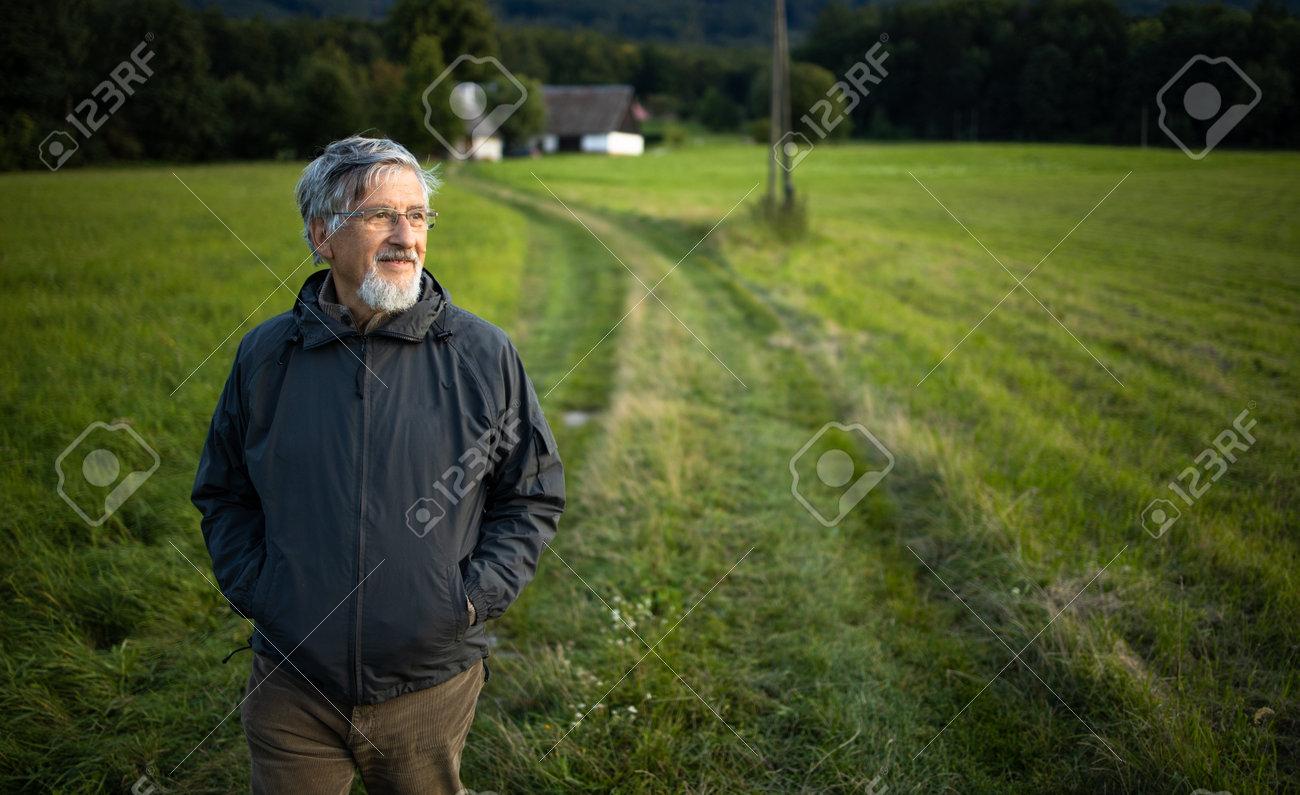 Senior man enjoying the outdoors, hiking, walking through lovely nature - 171623518