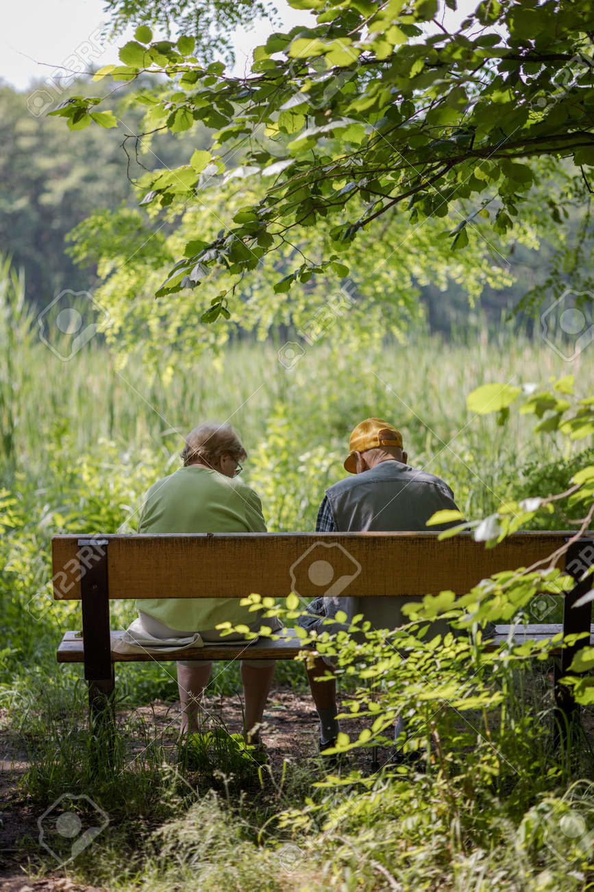 Elderly couple outdoors in summer. Happy elderly couple on a walk. Handsome man and woman senior citizens. Husband and wife of old age against the background of nature. - 171623523