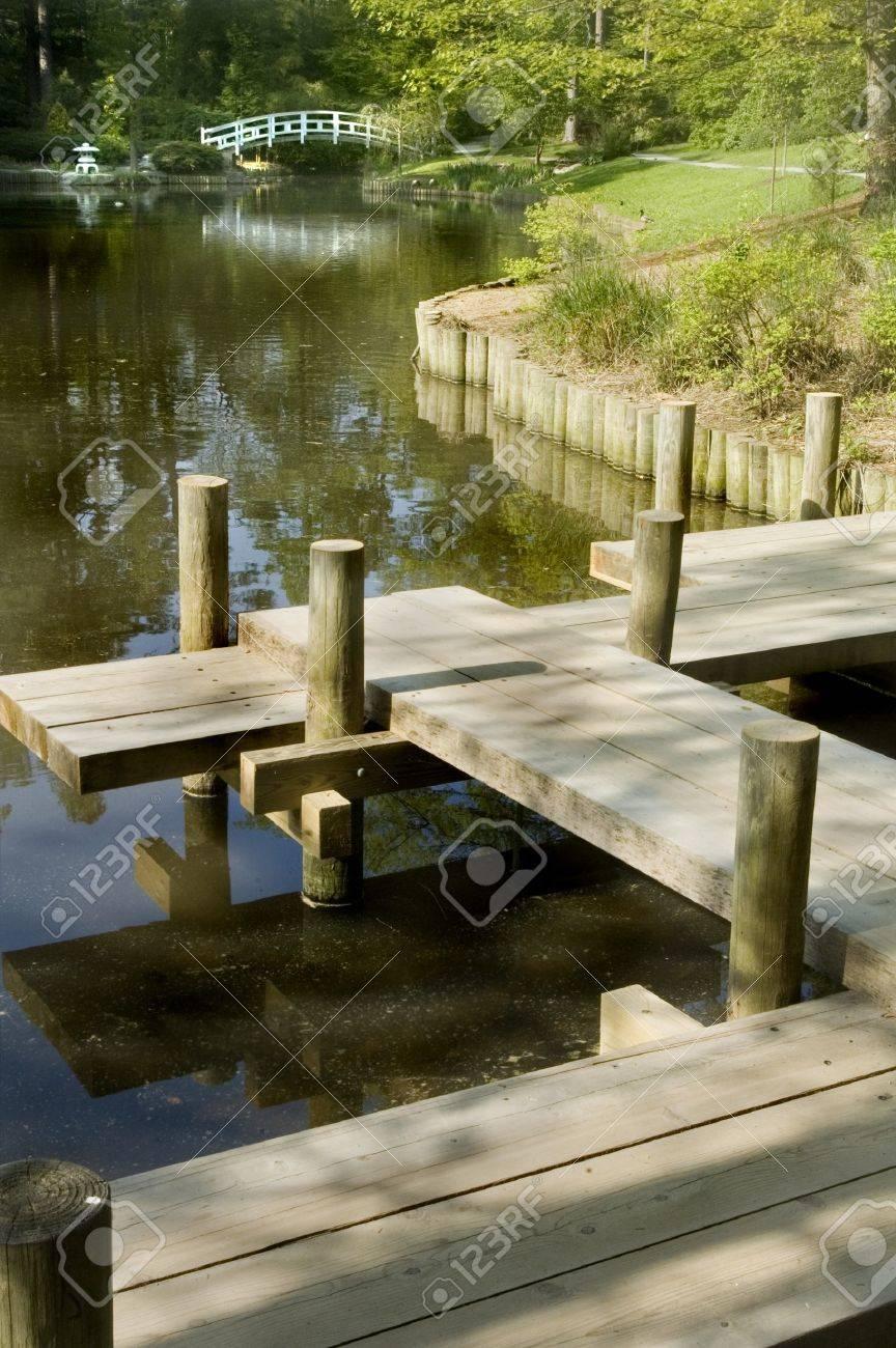 Japanese zen gardens with pond - Japanese Zen Garden Boardwalk Over Koi Pond Arched Moon Bridge In Background Stock Photo 7400209