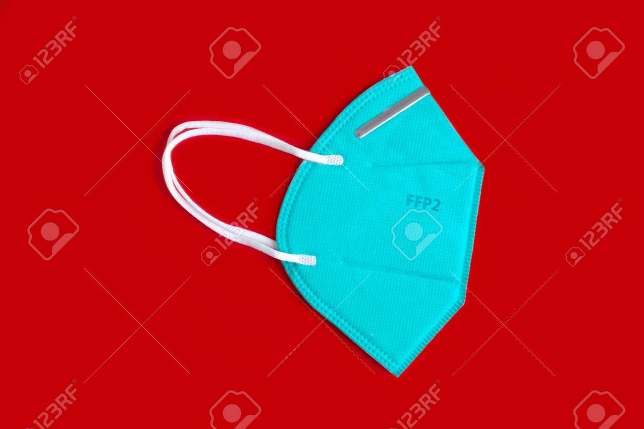 Side view of green FFP2 n95 protective face mask, virus prevention. Isolated on red background. - 163977359