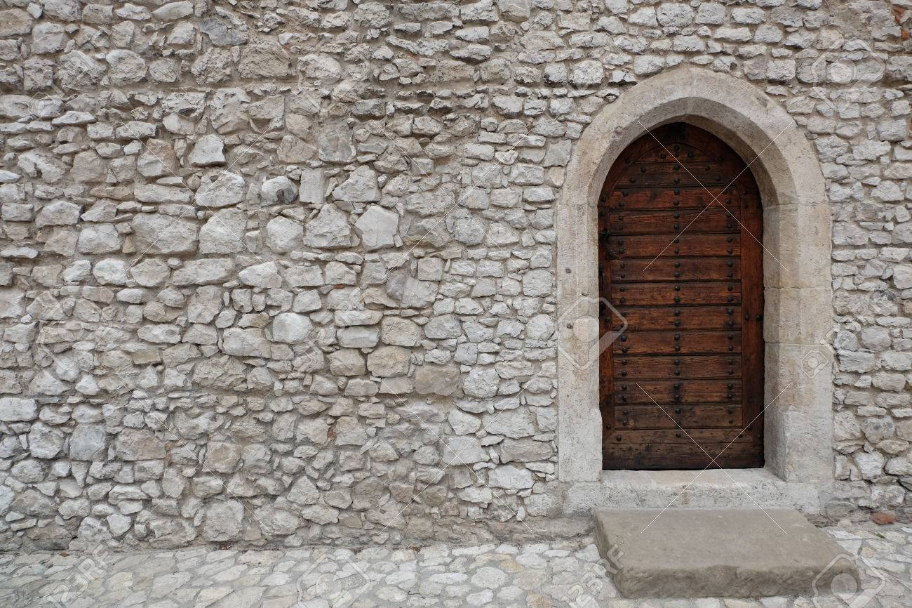 Fortress Or Castle Wall Made Of Stacked Stone Blocks And A Wooden Door With Gothic Style