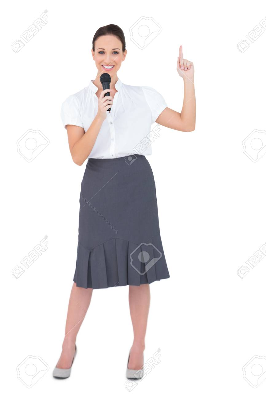Smiling attractive presenter holding microphone while posing on white background Stock Photo - 21765551