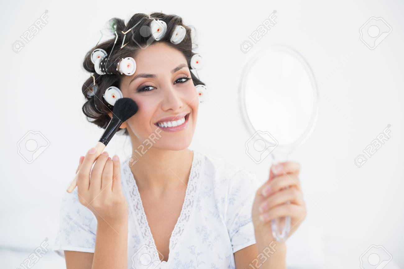hand holding mirror. Smiling Brunette In Hair Rollers Holding Hand Mirror And Applying Makeup At Home Bedroom Stock