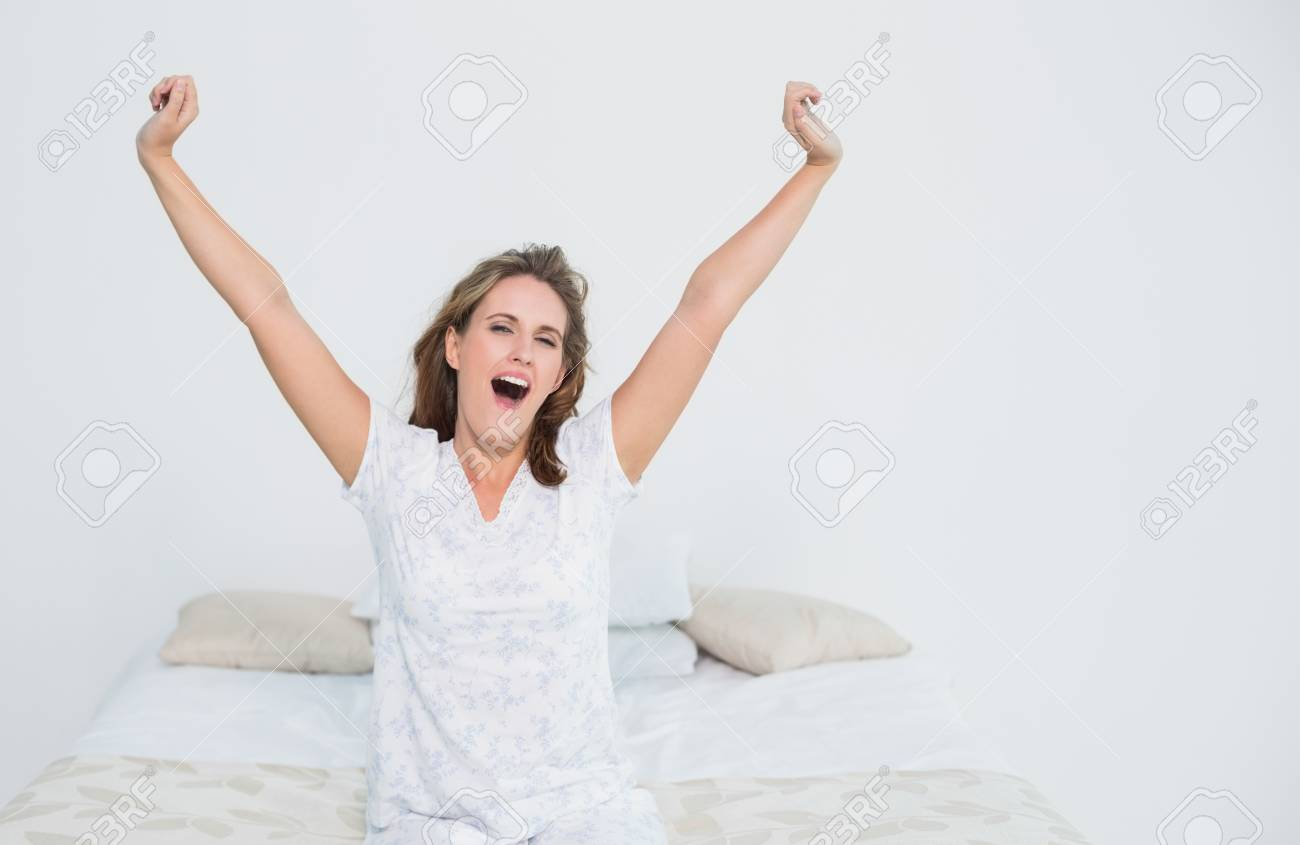 Pretty woman in bed stretching when waking up Stock Photo - 22324642