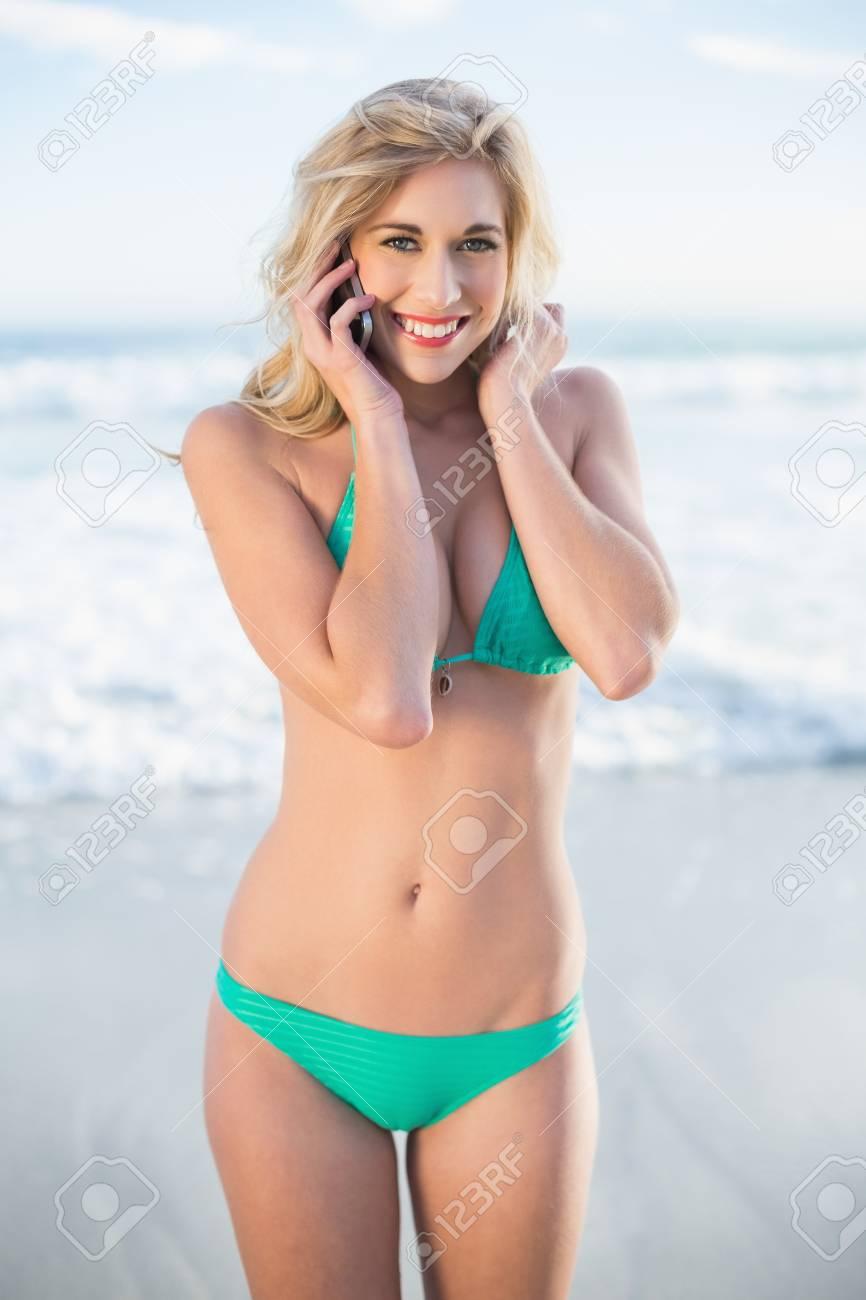 efe7905a710 写真素材 - 緑のビキニ ビーチで彼女の携帯電話を呼び出すに金髪の女性を楽しませ