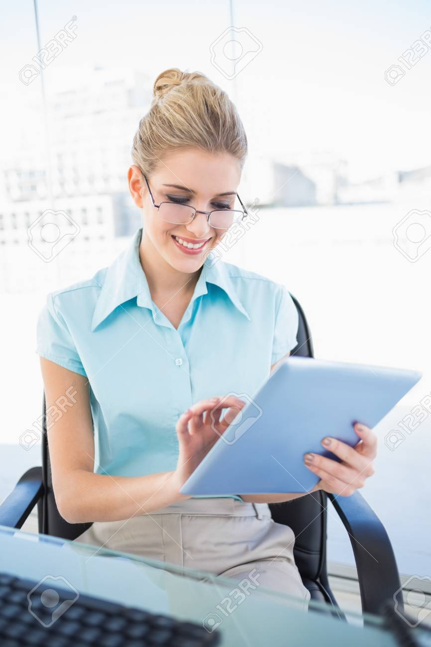 Cheerful businesswoman wearing glasses using tablet in bright office Stock Photo - 22341405