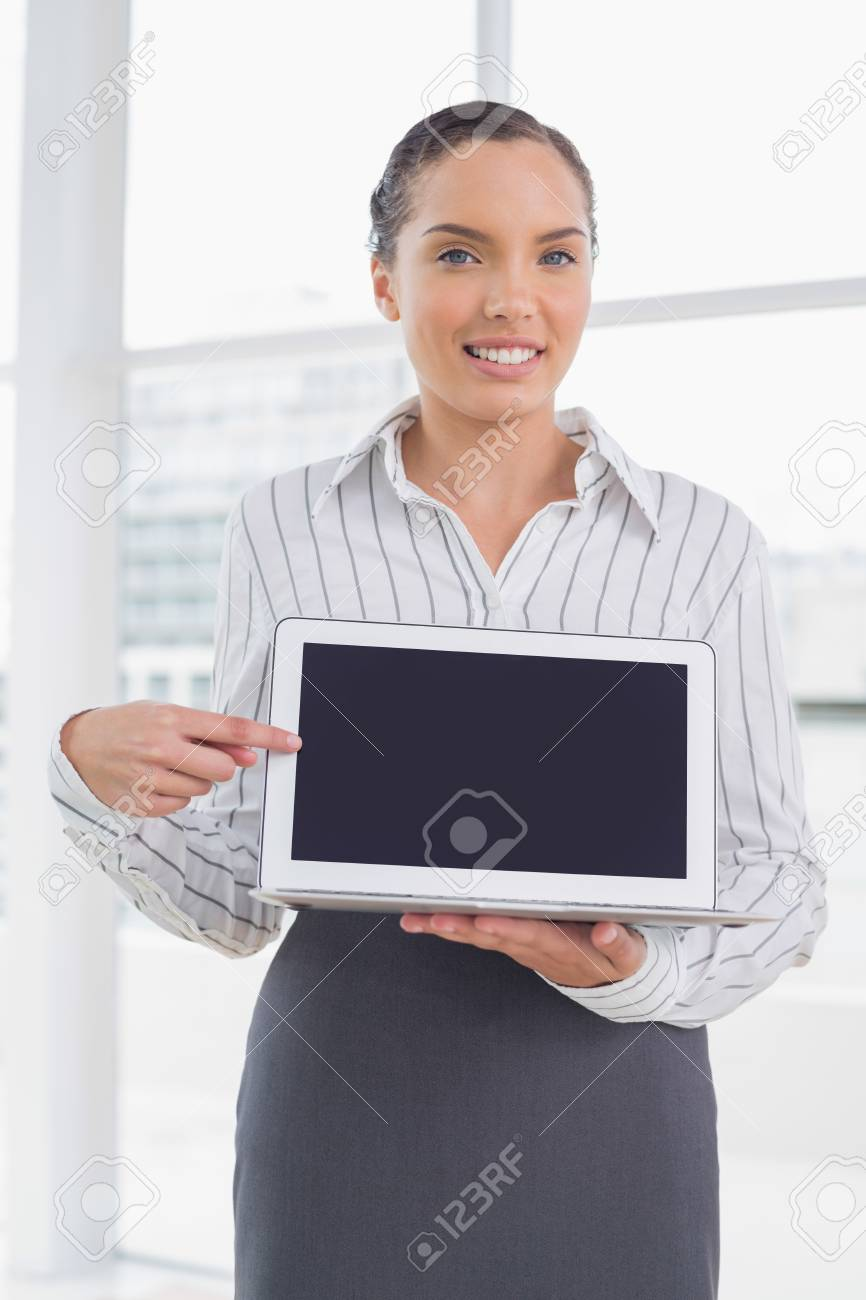 Attractive businesswoman showing laptop screen and pointing at it while looking at camera Stock Photo - 25402560