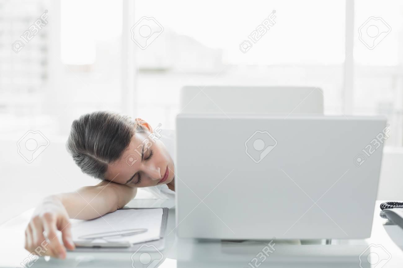 Jolie affaires épuisé assise à son bureau de dormir dans son