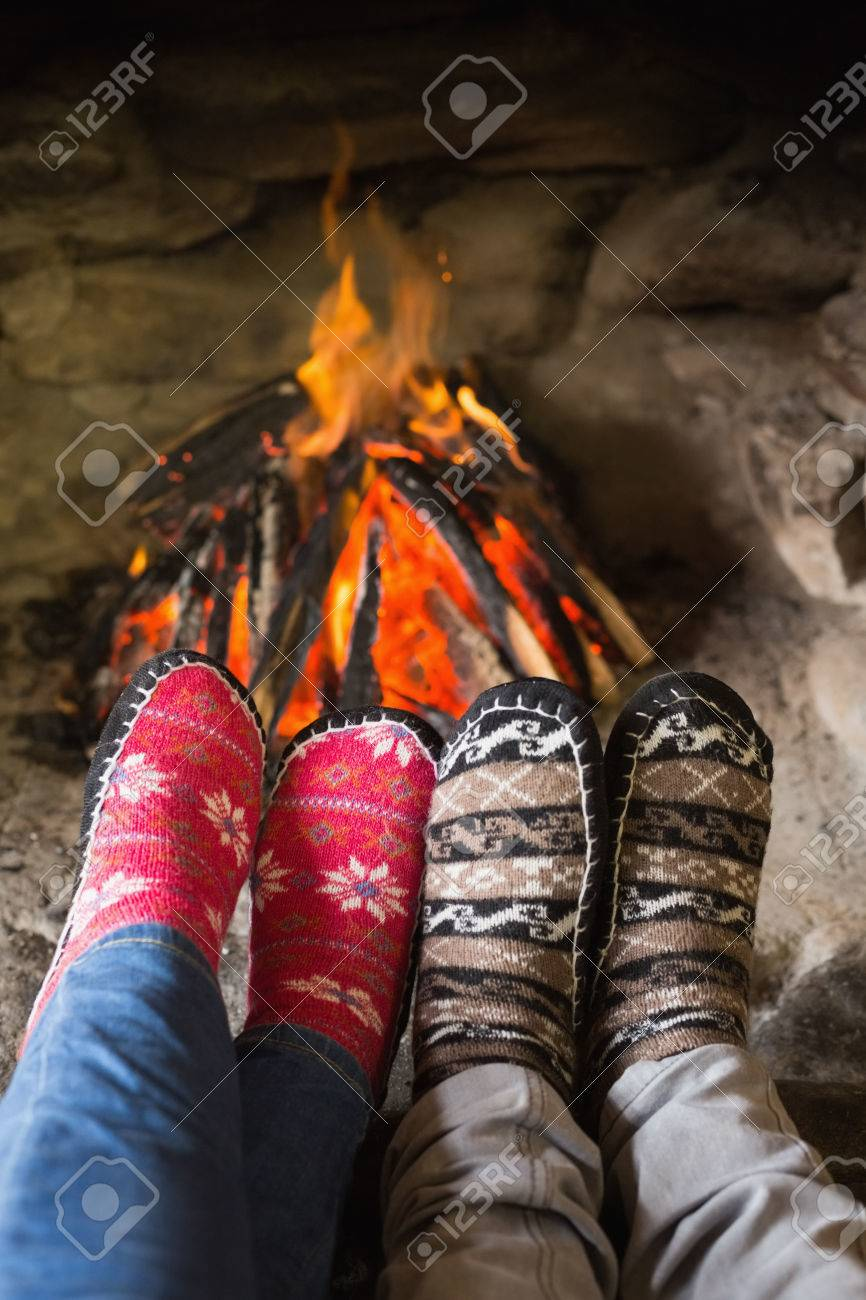 close up of romantic couples legs in socks in front of fireplace