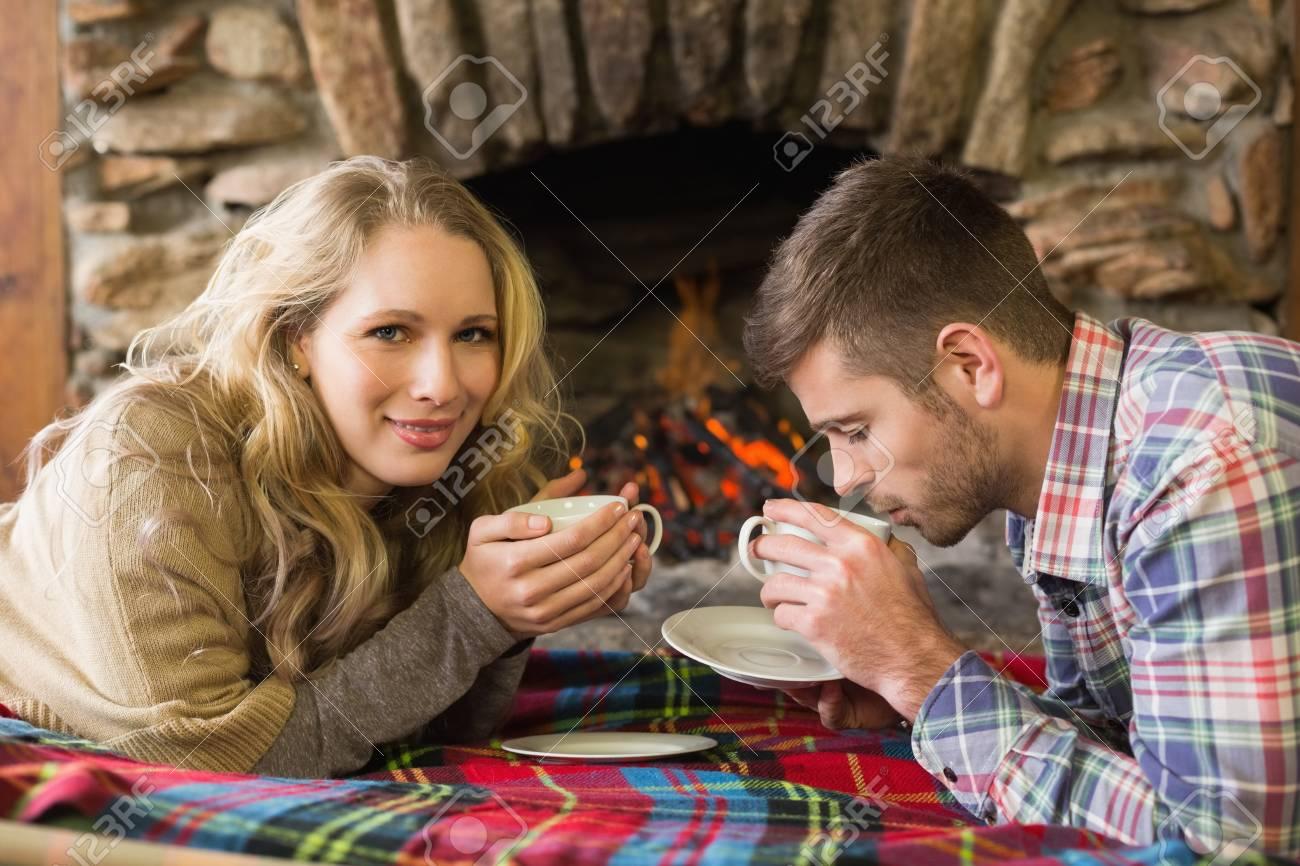 Foto Di Un Camino Acceso vista laterale ritratto di una giovane coppia con tazze di tè davanti al  camino acceso
