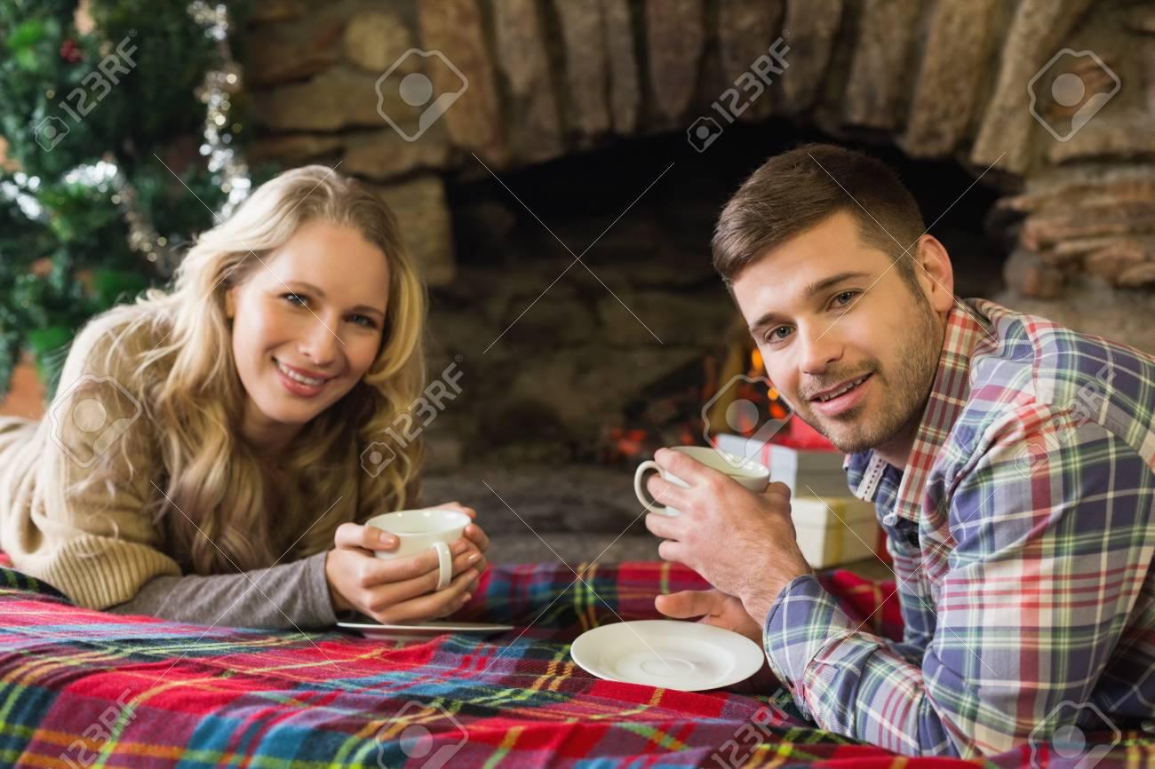 Foto Di Un Camino Acceso ritratto di una giovane coppia sorridente con tazze di tè davanti al camino  acceso