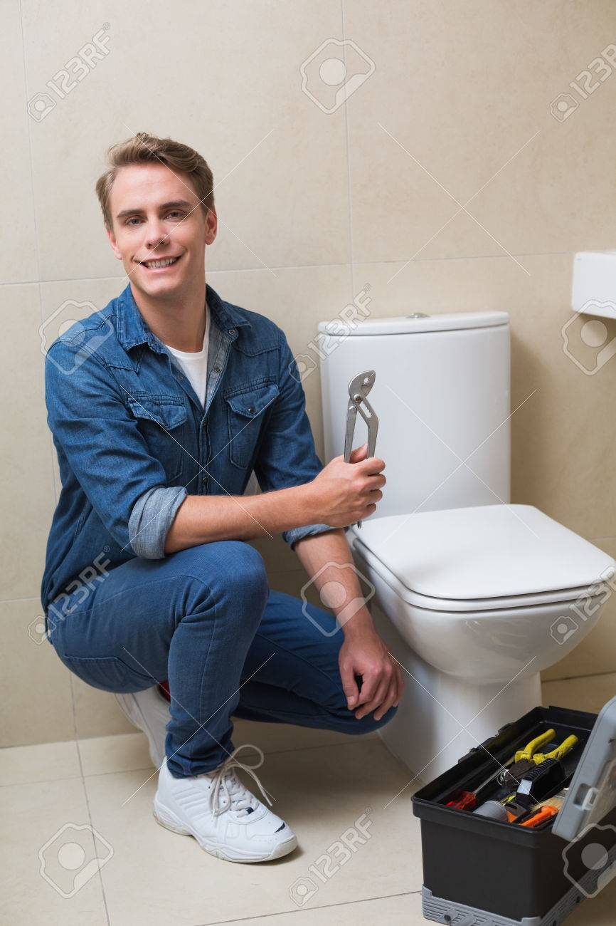 Portrait Of A Smiling Handsome Plumber With Toolbox Doing Toilet ...