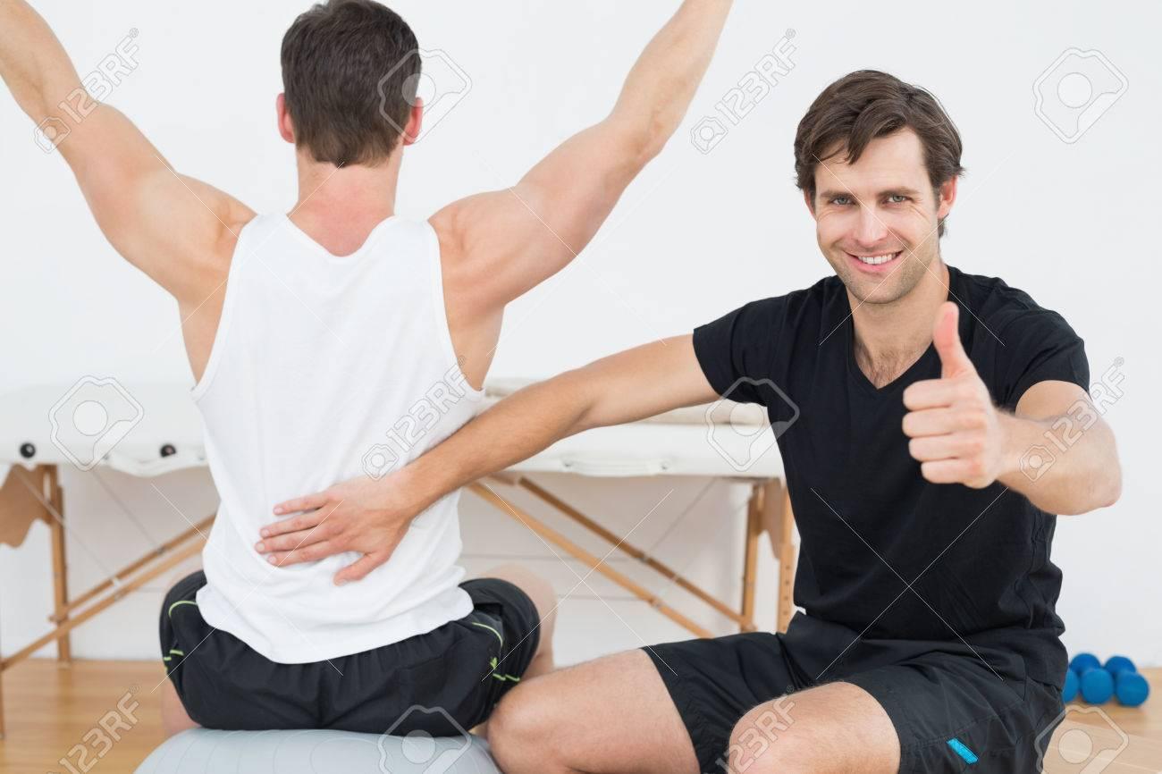 Fisioterapeuta gesticula los pulgares para arriba además del hombre en la  bola de la yoga Foto 16be95d5a8cf