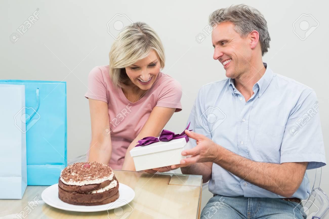 L Uomo Dà Una Donna Felice Un Regalo Di Compleanno Accanto A Torta E Borse Per La Spesa A Casa